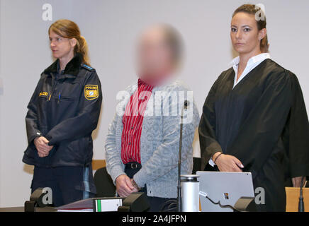 Augsburg, Germany. 15th Oct, 2019. A defendant (M) stands next to his lawyer Martina Sulzberger (r) in a courtroom of the Criminal Justice Centre. The farmer from Northern Swabia has been standing before the Augsburg Regional Court since Tuesday because he is said to have knocked his wife unconscious and then poured liquid manure over her until she suffocated. The man denies the crime. Credit: Karl-Josef Hildenbrand/dpa - ATTENTION: The accused was made unrecognizable on personal rights grounds/dpa/Alamy Live News - Stock Photo