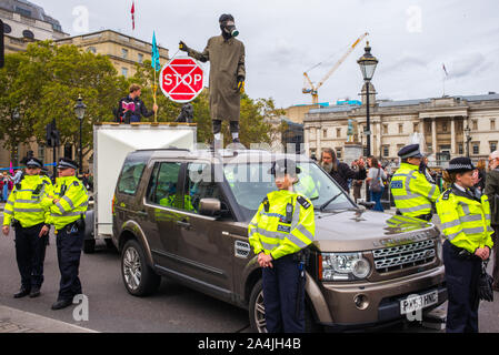 An Extinction Rebellion protestor stands on top of a car holding a red Stop sign while surrounded by police in fluorescent yellow jackets,London, 7 October 2019