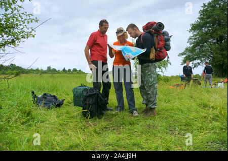 three tourists look at a map, a woman and two men study a tourist route, Kaliningrad region, Russia, June 16, 2019 - Stock Photo