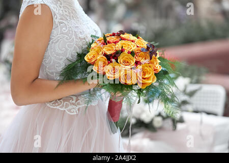 Bride in a beautiful white dress goes holding a wedding bouquet of orange roses in her hands. - Stock Photo