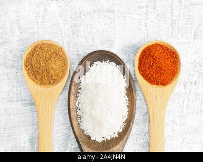 Spices and herbs set on concrete background in wooden spoon. Masala, mustard, chili pepper. Modern apothecary, naturopathy and ayurveda concept. - Stock Photo