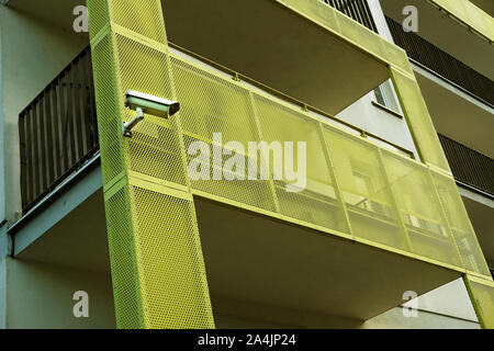 security cctv camera installed on a balcony of an apartment building in a residential area in Poland monitors the surroundings of the building - Stock Photo