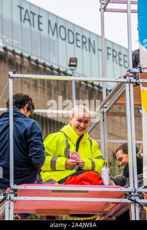 London, UK. 15th Oct, 2019. Extinction rebellion set up structures outsde the front of the Tate Modern as the preview of the Nam June Paik exhibitiongoes on inside. They are quickly surrounded by the City of London Police and threatened with arrest if tehy do not come down. Credit: Guy Bell/Alamy Live News - Stock Photo