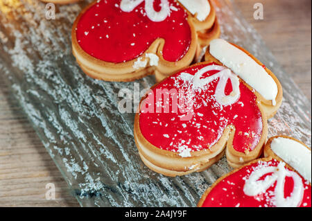 Homemade christmas ginger cookies in the form of red mittens on a glass plate on a wooden table. Christmas card. - Stock Photo