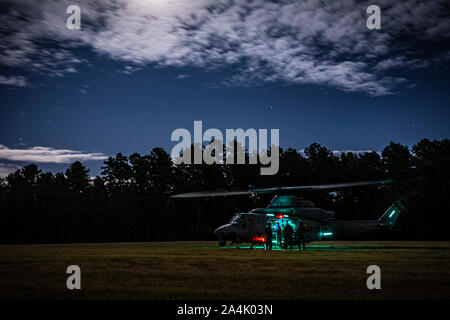A U.S. Marine Corps Reserve UH-1Y Venom with Marine Light Attack Helicopter Squadron 773 gets ready for fast rope insertion night training with Special Warfare Airmen assigned to the New Jersey Air National Guard's 227th Air Support Operations Squadron on Joint Base McGuire-Dix-Lakehurst, N.J., Oct. 10, 2019. (U.S. Air National Guard photo by Master Sgt. Matt Hecht) - Stock Photo