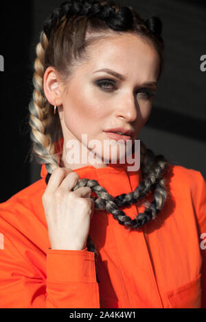 portrait of a beautiful working woman in orange clothes - Stock Photo