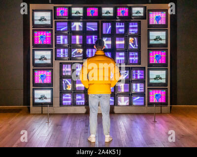 London, UK. 15th Oct, 2019. Video Commume 1970 and other installations in the Transmission room - Nam June Paik at Tate Modern. This exhibition presents a comprehensive overview of the visionary artist's five-decade career, bringing together a diverse array of works from rarely seen early compositions and robot sculptures to large-scale television installations and full-room installations, in a 'riot' of light and sound. He is enowned for his innovative use of emerging technologies. Credit: Guy Bell/Alamy Live News - Stock Photo