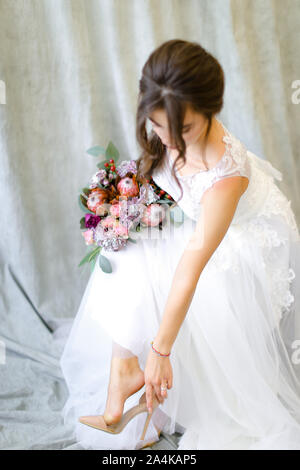 Young bride with flowers putting on shoes at photo studio. - Stock Photo