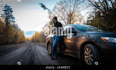 Chelyabinsk Region, Russia - October 2019. Successful young man with key standing near car. Photo noise - Stock Photo
