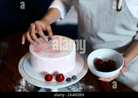 woman putting berries on dessert, art , creativity, close up cropped photo - Stock Photo