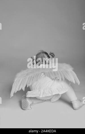 Small girl wearing angel costume crawling on floor - Stock Photo