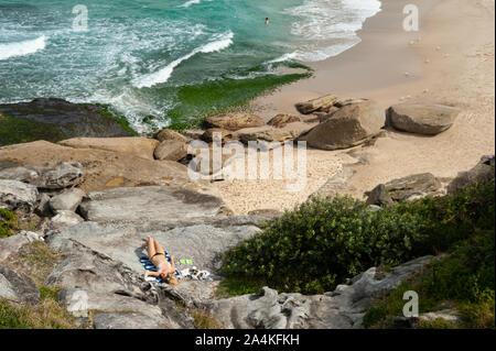 27.09.2019, Sydney, New South Wales, Australia - A woman sunbathes on the rocks at Tamarama Beach. - Stock Photo