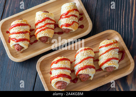 Sausage rolls on the wooden tray: top view