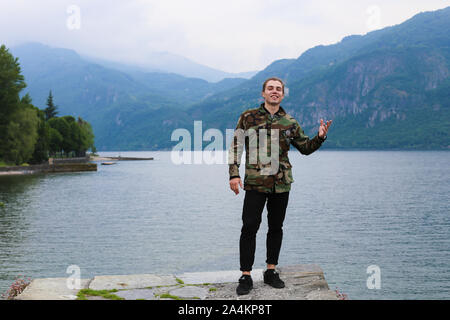 Happy young man wearing camouflage jacket standing with lake Como and mountain in background. - Stock Photo