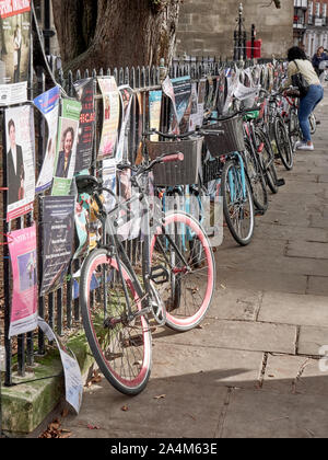 Cambridge, UK - October 9, 2019: Bicycles parked against the fence with a lot of posters. - Stock Photo