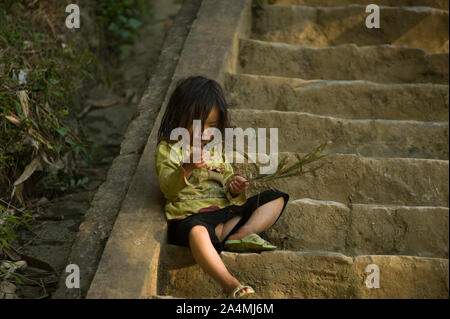 Sapa, Lao Cai, Vietnam - March 21, 2011: Cute little girl of Hmong ethnicity crying alone in the rocky ladder of traditional village around Sapa - Stock Photo