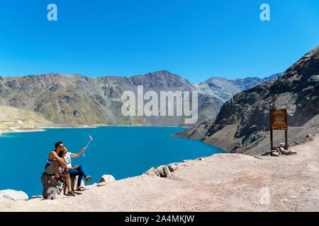 Chile, Andes Mountains. Young couple taking a selfie with a selfie stick at the Embalse el Yeso (El Yeso Dam), Andes Mountains, Chile, South America - Stock Photo