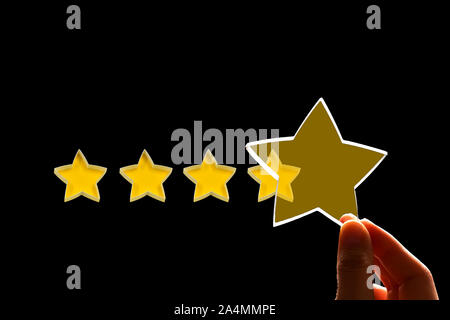 A woman gives a fifth star rating, the concept of a positive rating, reviews and feedback on black background. - Stock Photo