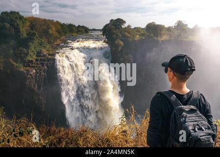 Tourist looks at the Victoria Falls on Zambezi River in Zimbabwe - Stock Photo