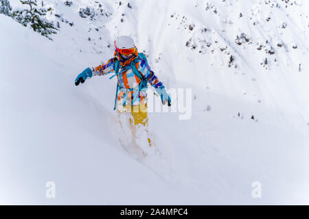 Young athlete girl in helmet and mask is riding on snowboard on snowy slope at winter day. - Stock Photo