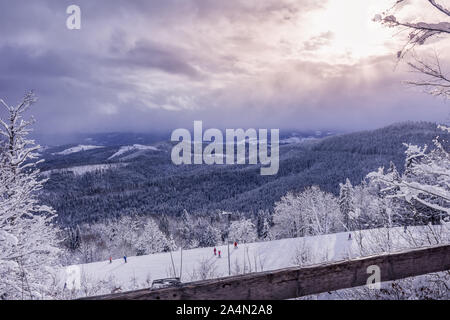 Carpathian mountains and Bukovel ski resort slope. Few unidentifiable hobby skiers are enjoying their active holidays. Wooden fence at foreground. Act - Stock Photo