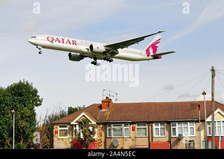 A Qatar Airways Boeing 777-300 jet flying low over rooftops at Hatton Cross on it's landing approach to Heathrow London England UK - Stock Photo