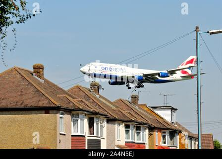 A British Airways jumbo jet flying over rooftops at Hatton Cross about to land at Heathrow Airport London England UK - Stock Photo