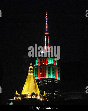 New york, New York, USA - 1 January 2016: The top of the Empire State building is light up in green and red for Christmas behind the Gold top of the C - Stock Photo