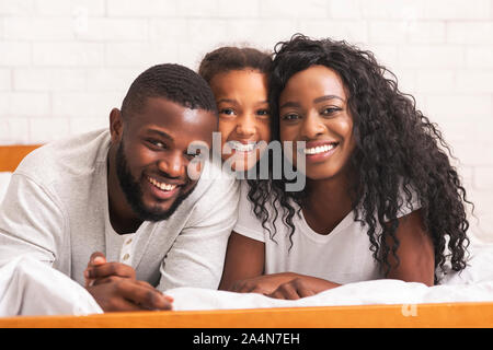 Portrait of beautiful african american family lying on bed together - Stock Photo