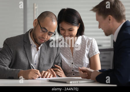 Happy diverse couple signing contract, making purchase deal - Stock Photo