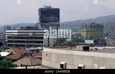 5th June 1993 During the Siege of Sarajevo: the view north-west from Stolačka Street. The burned-out tower block of the Building of the BiH Parliamentary Assembly dominates the frame with the Holiday Inn Hotel on the right. In front of the Assembly Building are the ruins of the old tobacco factory. - Stock Photo