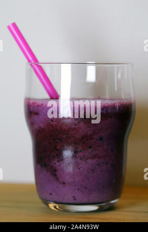 Healthy and delicious homemade smoothie(s) on a table with straws. Closeup still life image. Berries, fruits and veggies in yummy drink form. - Stock Photo