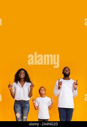 Beautiful Black Family Pointing Fingers Upwards At Copy Space - Stock Photo