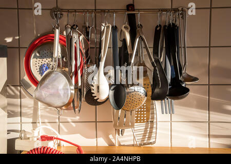 Various kitchen utensils, ladles, spoons, sieves, pliers, in a private kitchen, - Stock Photo