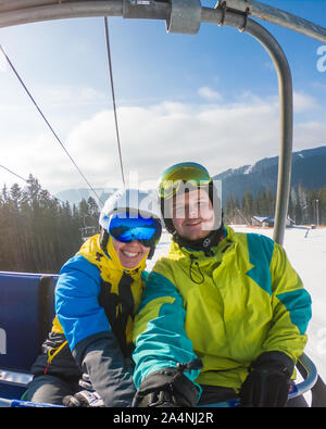 couple taking selfie in ski equipment while lift up to hill - Stock Photo