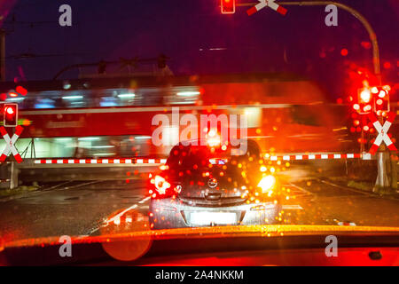 A car waits in front of a closed railway barrier while a local train passes by, rain weather, darkness, - Stock Photo