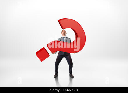 Full portrait of a businessman holding big red 3d question mark isolated on white background - Stock Photo