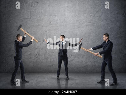 Businessman separating two fighting businessmen with hammers - Stock Photo