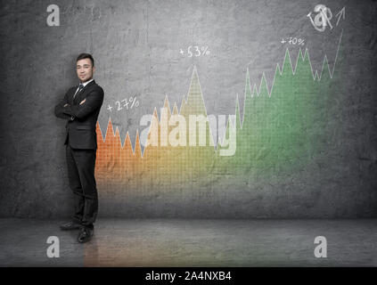 Full portrait young businessman with his arms crossed on background of an increasing graph - Stock Photo