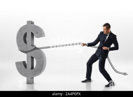 Businessman pulling big concrete 3d dollar sign with a rope isolated on white background - Stock Photo