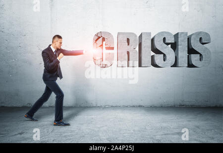 Businessman standing on ground hitting word 'CRISIS' with fist - Stock Photo