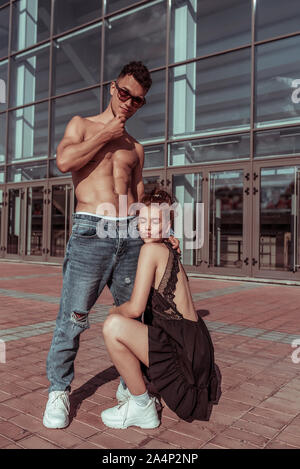 Young couple, guy girl, dancers, hip-hop summer city, background glass windows. Active youth lifestyle, fitness concept passion love kisses. Athletic - Stock Photo