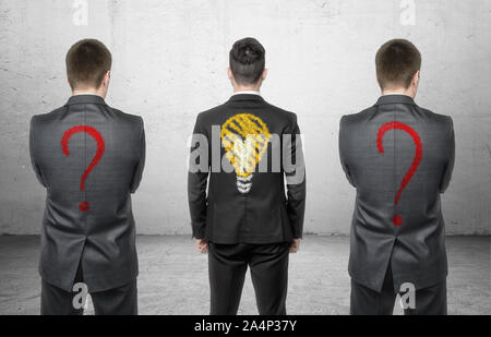 Three businessmen standing with drawing of light bulb and question marks on his back - Stock Photo