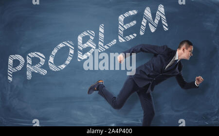 Rendering of businessman running to escape the word 'problem' written on dark blue wall. - Stock Photo