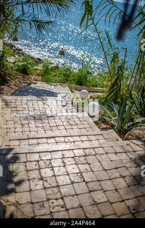 a stone staircase leads through a passageway down to the sea - Stock Photo