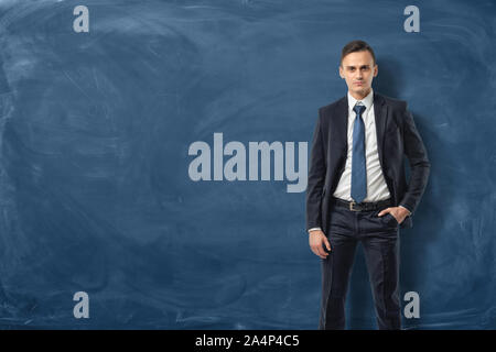 Businessman in suit standing and confidently looking forward with his hand in pocket