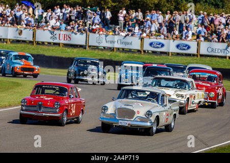 Madgwick Corner with cars of the St Mary's Trophy race at the 2019 Goodwood Revival, Sussex, UK. Spectators in the background. - Stock Photo