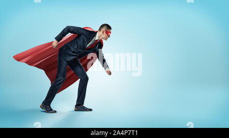 A businessman in a superhero red cape and a mask standing in starting line position on blue background. - Stock Photo