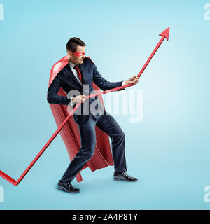 A businessman wearing a red superhero cape trying to hold a red statistic arrow with force on blue background. - Stock Photo