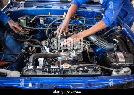 African Mechanics repairing a vintage car engine with carburetor - Stock Photo